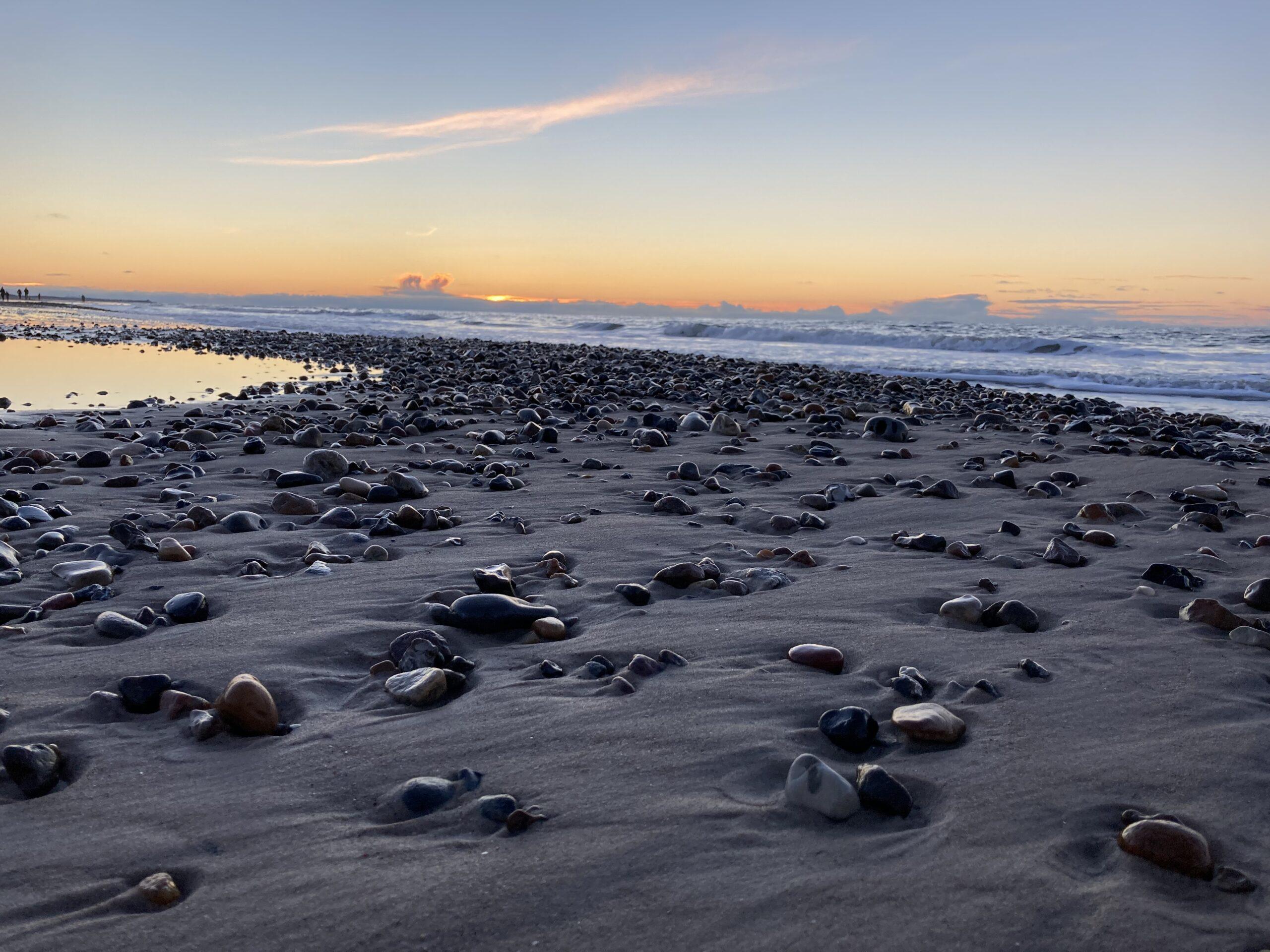 Solnedgang den 26. januar 2021 ved Tornby Strand. Smukke sten med bølger i baggrunden.